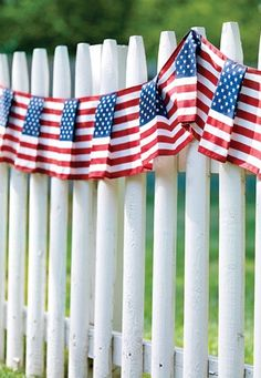 Flags on white picket fence