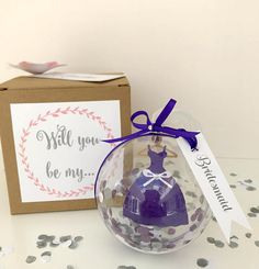 Will You Be My Bridesmaid Dress Bauble ******************************************** A perfect gift to give your Bridesmaids, Flowergirls and Maid of Honour A beautiful surprise to reveal their role on your Wedding Day. Each gift box is personalised with Will you be my.... and a personalised name tag of your guest finished with a paper flower. Inside the box the bauble reveals your guests role via your chosen role tag and coloured dress. Each bauble contains a hanging card dress, embellished…