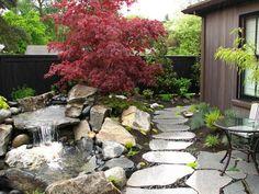 petite cascade de jardin en pierres naturelles, allée en dalles et érable japonais à feuillage rouge