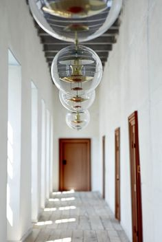 """Verner Panton's unique """"Globe"""" pendant was designed for a furniture fair in Germany in 1969. However, it was first put into production seven years later. The lamp consists of a round ball in transparent acrylic with 5 reflectors inside. It was originally designed with reflectors coated in white, blue and orange."""