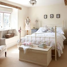 A soft cream backdrop, ornate metal bedstead and a collection of pretty accessories create a feminine feel in this pretty coungry bedroom. A reclaimed painted bedside cupboard and elegant scatter cushions introduce subtle blue/grey accents that make the room distinctive