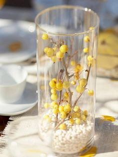 Looking for an inexpensive, yet chic fall vase filler? Try dried beans. This pantry staple is readily available in bulk at a low cost. For this arrangement, we filled a hurricane vase with about two inches of white beans and added a branch of yellow berries. Experiment with different color combinations, such as red kidney beans with orange berries. #Cake