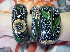 Conjunto com 03 pulseiras de madeira com estampa <br>Dimensões: 6,5 cm interno