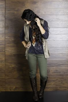 Outfit features: Spur Cross 3/4 Hi Low Top (https://www.notw.com/products/girls-fashiontops-spurs-cross-341975/) - Paired with military green denim, khaki vest, long beaded necklace and riding boots.