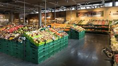 Im Eingangsbereich empfängt die Kunden eine geballte Ladung Frische: Obst und Gemüse wird üppig, zum Teil in Holzkisten, präsentiert. Holz dominiert auch an Wänden und Regalen, der dunkle Steinfußboden ist aus Tessiner Granit. All dies soll eine Marktstimmung erzeugen, so die Coop.