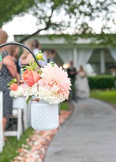 White and coral flower petals with jars of white hydrangea coral white and coral flower petals with jars of white hydrangea coral roses and dahlias and variegated pittosporum line the aisle to the gazebo where c mightylinksfo
