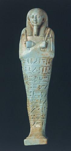 Oushebti de Neferibrêsaneith Amasis (6e s. av. JC) Céramique siliceuse émaillée bleu-vert, décor gravé (outils). Forme : momiforme, pilier dorsal, socle quadrangulaire Haut.: 18.5 cm; larg.: 4.9 cm; ép.: 3.2 cm Découverte : Nécropole de Saqqarah (probablement)