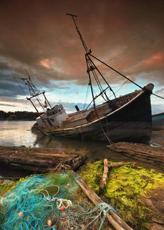 An old fishing trawler left to decay, with it's fishing nets abandoned nearby