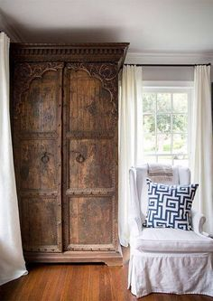 An Antique Cedar Armoire Stands In A Corner Of Living Room