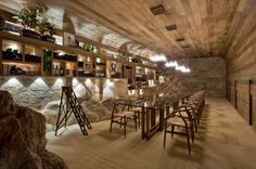 Wine cellar in home cut into hillside takes advantage of stone outcroppings...
