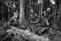 22 Nov 1967, Dak To, South Vietnam --- November 22, 1967 - Dak To, South Vietnam: Plasma is given to a wounded member of the 173rd Airborne Brigade on a ridge on Hill 875 November 21, 1967 as another member races into battle. U.S. paratroopers November 22, 1967 stormed up Hill 875 and smashed into the Communist hilltop fortress that kept them trapped for three days. They hurled grenades and fired flamethrowers into North Vietnamese bunkers still being bombarded by army artillery and jet…