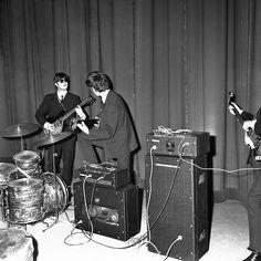 Members of the Beatles John Lennon and George Harrison, turned away, talking in Versailles, France on Jan. 15, 1964. (AP Photo/Tellier)