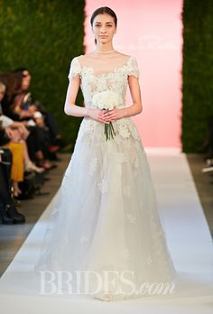 Brides.com: . Chantilly lace A-line wedding dress with short sleeves, an illusion neckline, and floral embroidered details, Oscar de la Renta