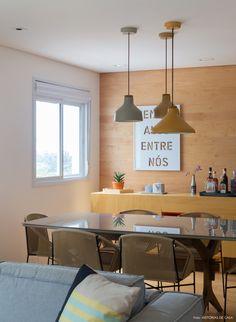 sala de jantar com parede de madeira, móveis contemporâneos e cores claras, inspirada no estilo escandinavo