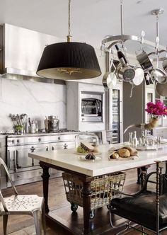Beautiful kitchen with white marble, a fab white La Cornue, and a French baking table used as an island.