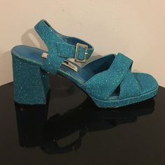 """DIBA Turquoise Glitter Ankle Strap Heeled Sandals Up for grabs is this pair of shoes from DIBA. They are a size 8M with 0.5"""" platform soles and 3.75"""" block heels. These sandals have ankle straps with buckle closures and wide crossover toe straps. They are turquoise blue glitter and platform soles. This is actually a second pair of this shoe that I've owned. The other pair I wore a lot in my younger days. They were very comfortable to dance and walk in. These platforms are new in the original…"""