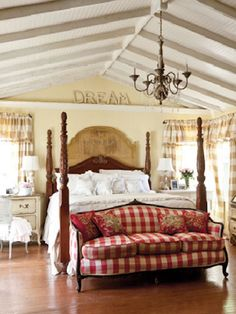 A wooden, four-poster bed grounds this master bedroom, while a red-and-white gingham settee adds a playful touch.