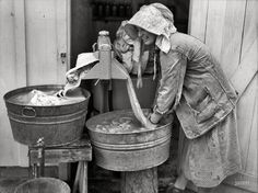 "May 1938. Irwinville Farms, Georgia. ""Mrs. Coleman doing a washing."" by John Vachon for the Resettlement Administration."