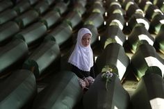 Ema Hasanovic, five, leaves flowers on the coffin of her uncle at the Srebrenica Genocide Memorial in Bosnia.