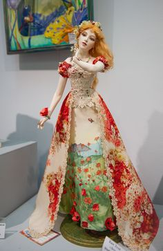A repin of a woman doll, Vahtanov, a redhead with a beige and red dress - The link goes to a locked doll board.