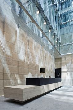 171 Collins Street, Melbourne By Bates Smart.  Monolithic limestone walls and desk with black steel accents and custom lighting.  Looking for an overall neutral palette with shocks of focus