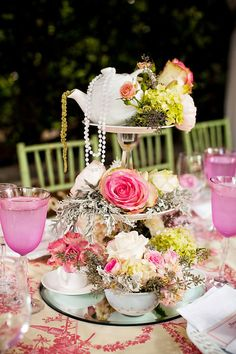 Elaborate bridal shower centerpiece with roses, tea cups, and tea pots on vintage tiered stand.