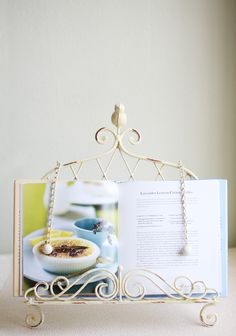"""Singing Sparrow Cookbook Stand 32.99 at shopruche.com. Crafted with antiqued details, this iron cookbook stand in muted ochre is perfect for holding your page and keeping your hands free.13.5"""" L x 3"""" W x 16.5"""" H"""