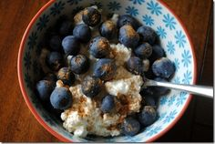 a small bowl of cottage cheese, topped with blueberries and pumpkin pie spice