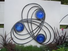 Forged steel and blown glass Wall Mounted or Wall Hanging sculpture by artist Jenny Pickford titled: 'Celtic Screen (Steel and Glass Floral Suspended/Hung statues/sculpture)'