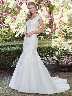 Rebecca Ingram - victoria anne, Pretty and demure, this tulle fit-and-flare wedding dress features lace appliqués cascading over the bodice and modest cap-sleeves. A V-neckline and flowing train evoke timeless elegance. Finished with covered buttons over zipper and inner elastic closure.