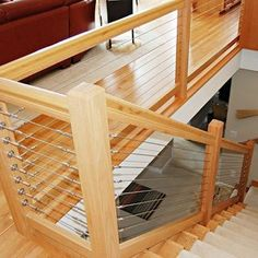 """The Next Level: 14 Stair Railings to Elevate Your Home Design — contemporary wood and stainless steel (homedit.com via Yahoo! Homes) (""""The natural beauty of wood marries the streamlined look of stainless steel cable in this DIY-friendly railing system. This contemporary stair rail requires no special tools and is appropriate for use both indoors and out."""") (I love the wood framing, but I would rather have solid sheets of frosted/opaque glass instead of all the cables.)"""