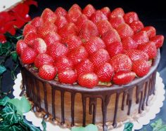 2-layer chocolate cake with chocolate buttercream and chocolate dripping down sides with fresh strawberries covering top of cake.