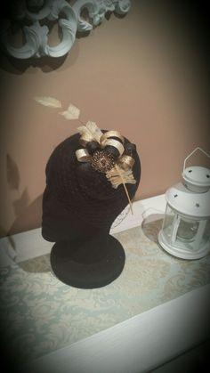 Tocado casquete negro con lazos de sinamay dorado,beige y negro, pluma flecha y broche de pedrería dorado