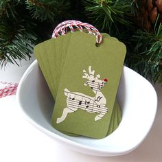 These darling Musical Reindeer Christmas Tags are the perfect finishing touch for your holiday packages. Affix them to gifts, goodie bags. wine bottles or other holiday treats. Each one features a reindeer die-cut from antique sheet music with a red glitter nose on a Moss Green tag. The
