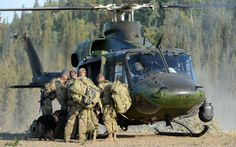 """Members of the RCMP Emergency Response Team and police dog """"Taz"""", prepare to board a Canadian Forces CH-146 Griffon helicopter from 400 Tactical Helicopter Squadron, Borden, ON, during a CF assistance to RCMP scenario in Tsiigehtchic, NT, on Operation NANOOK 2012.  Photo credit: Sgt Frank Hudec, Canadian Forces Canada Command © 2012 DND-MDN Canada  #StrongProudReady Military Helicopter, Military Police, Military Aircraft, Force Pictures, Emergency Response Team, Military Working Dogs, Canadian Army, Police Dogs, Search And Rescue"""