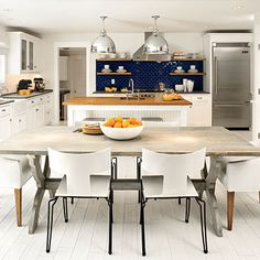 If color isn't your thing, take your palette to the other extreme by keeping all of your surfaces, from ceiling to floor, a refreshing white. Details such as painted wood floors and beaded-board cabinet fronts add casual beach house styling. Warm wood accents, a navy tile backsplash, and stainless steel accents add a simple layer of color and texture that gives this kitchen a sophisticated look.