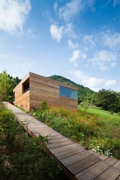Built along a grassy hillside, the Skyward House blends beautifully into the woodsy environment while providing protection from the busy street below. The living areas of the residence were built higher in the Kazuhiko Kishimoto-designed home to help provide comfort to the homeowner as this was intended to be her final home.