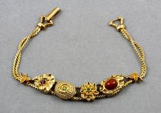 Vintage Goldette NY Victorian Revival Wired Slide Charm Bracelet.  Victorian Revival charm bracelet by Goldette of New York. Bracelet is unsigned, but it is a Goldette piece due to construction and quality. Bracelet features four large slide charms of various designs with Persian Turquoise, Carnelian, Seed Pearls, Emerald and Amethyst rhinestones on textured gold tone with fold over clasp. bracelet measures 1/2 wide x 7 5/8 long. Bracelet is in excellent condition with all its stones and no…