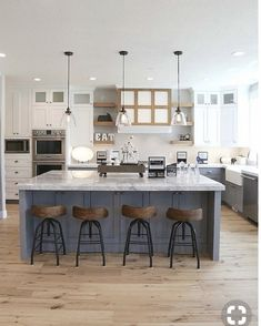 Dark blue island with gas cooktop and griddle, with grey cabinets and white counter tops