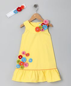 For girls who love to prance around prettily, this dress and headband set, with its energizing combination of colors, will instantly set feet to skipping. With buttons up the back, this frock goes on easier than little ladies can pluck flowers from the neighbor's garden.
