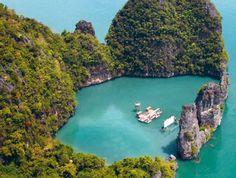 Sala de cinema flutuante em ilha paradisíaca naTailândia, localizada numa lagoa formada por rochas onde brotam de uma água verde esmeralda. A sala de cinema foi construída para um festival
