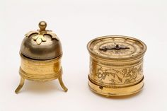Tudor Alarm Clock, produced around 1540-1589.   This drum-shaped gilt-brass table clock has a spring-driven movement, horizontal dial, single steel hand and chapter ring marked with Roman hour numerals I-XII. The clock has a separate alarm mechanism, which rests over the dial when in use. The alarm bell rings when the hand reaches the time at which the alarm is set and a detent (trip lever) is released. The clock is small and portable and the alarm can be detached when travelling. The drum…