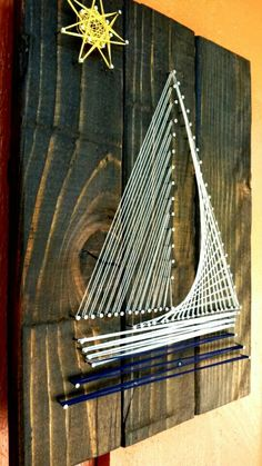 This is a string art sign I made by hand-cutting and staining a piece of wood. The wood is a dark brown stain. The sailboat is made with silver
