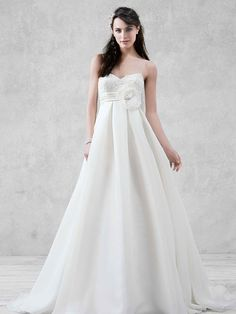 This satin-faced organza ball gown features a spaghetti strap lace bodice, figure flattering empire waist with detachable 3D floral flower, and box pleats. Galina Style KP3694. #davidsbridal #weddingdress