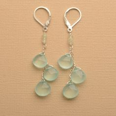 Aqua Blue Gemstone Earrings. Beautiful ocean green/blue chalcedony stones hang from sterling silver chain and leverback earwire to create these beautiful earrings. The stones dangle below a few yellow/green prehnite stones which sit just below the leverback adding both length and elegance to these special earrings.  Chalcedony is said to absorb negative energy and harmonize the mind, body and spirit.  Follow Izuly on Facebook and twitter for deals and promotions…