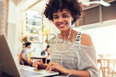 Portrait of happy young african woman with a laptop at cafe Smiling woman sitting in coffee shop wit Stock Photo