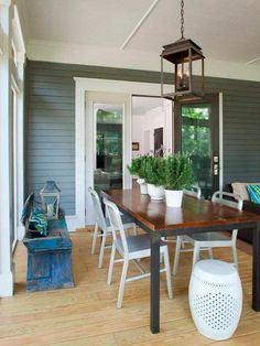 A trio of potted lavender plants are front and center in this sunroom's transitional dining nook, while a shabby chic bench echoes the home's exterior blue-gray hue.