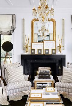 The contrast between fireplace and chairs works here. Note that the floor covering is also dark.  The mirror, sconces, and chandelier draw the eye upward..