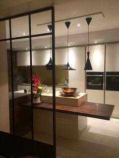 Une cuisine très épurée où le noir des luminaires design Beat Lights de Tom Dixon fait écho à la verrière métallique. Une réalisation délicate et très graphique signés par les concepteurs-décorateurs du magasin Arthur Bonnet de Caen.