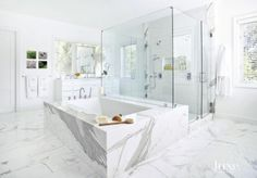 The light, ethereal bathroom features an Atlantis Whirlpools tub from Decorator's Plumbing, as well as a Calacatta gold marble tub surround. To maximize the tropical views, a small over-sink mirror was placed over one of the room's many windows. The vanity is by M Tec Custom Cabinets.